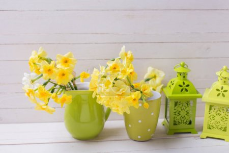 Yellow spring daffodils or narcissus flowers in green pitcher and decorative green lanterns on white wooden background. Selective focus