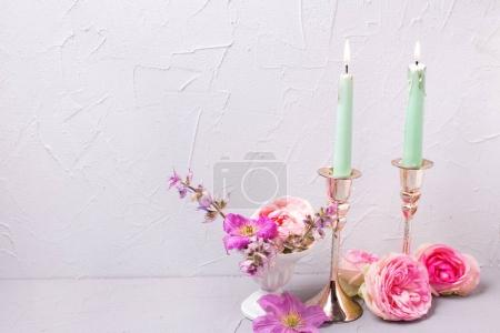 Two birning candles and  summer flowers