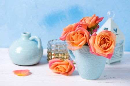 Bunch of fresh orange roses in cup  against blue wall. Place for text. Floral still life.