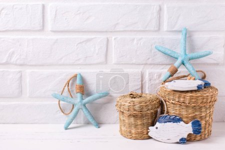 Decorative sea stars on white wooden background againstc white wall.  Place for text. Summer, vacation concept.