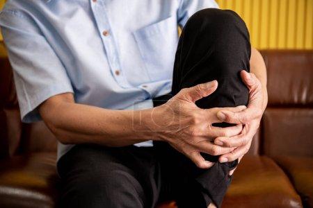 Älterer asiatischer Mann, der auf Safa saß, verletzte sich am Bein und berührte das Bein schmerzhaft.