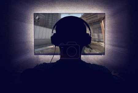 Photo for Gamer in headphones sits in front of a blank monitor in dark room - Royalty Free Image