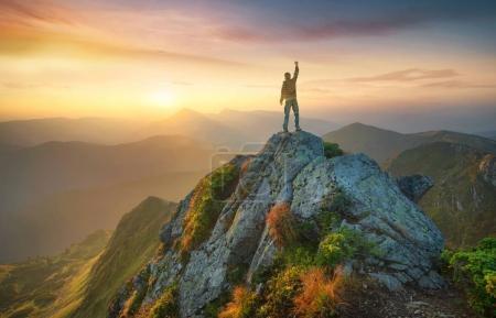 Tourist on the peak of high rocks.