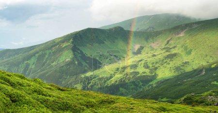 Rainbow under mountain ridge