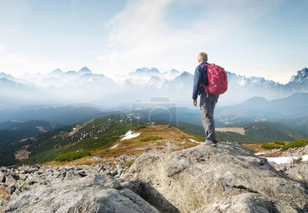 Mountain tourist on the high rock. Sport and active life concept