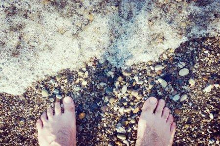 Photo pour Pieds nus d'un homme. Il est situé sur une plage de galets à côté de la vague de la mer. Mousses de l'eau. Photo en stock tonique. - image libre de droit