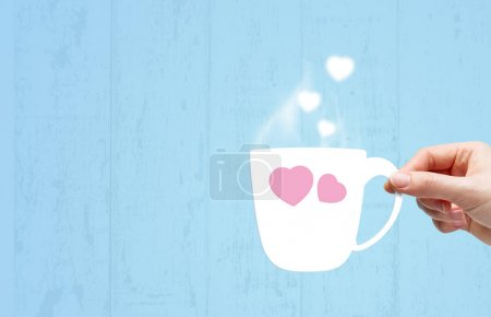 Young woman hand holding white paper cup with smoke heart shape