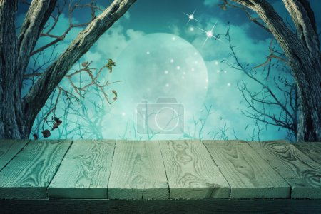Photo for Halloween background with empty wooden table over spooky trees - Royalty Free Image