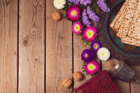 Foto de Jewish holiday Passover background with matza, seder plate and spring flowers. View from above - Imagen libre de derechos