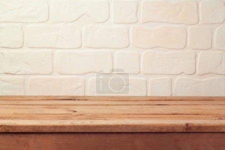 Foto de Mesa de terraza de madera vacía sobre fondo de pared de ladrillo - Imagen libre de derechos