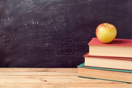 Photo pour Retour à l'école avec livres et pomme sur tableau - image libre de droit