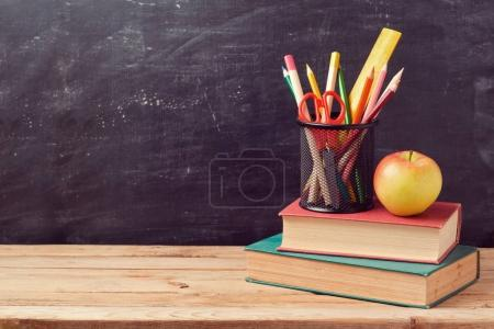 books, pencils and apple