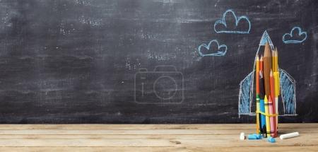 Photo pour Retour à l'école concept avec fusée issus des crayons sur fond de tableau - image libre de droit