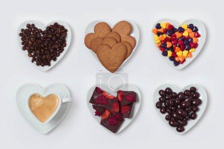 Photo pour Assiette en forme de coeur avec biscuits, bonbons, chocolats et tasse à café sur fond blanc . - image libre de droit