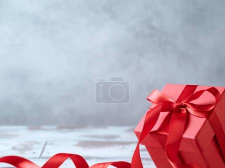 Gift box with red ribbon over grey background