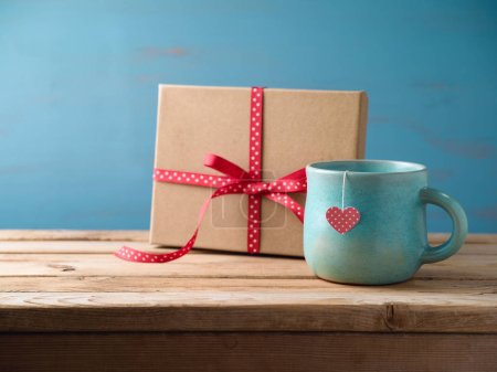 Tea cup with gift box on wooden table. Valentines day concept