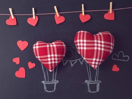 Valentines day concept with heart shapes as air balloons over chalkboard background