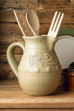 Kitchen utensils in ceramic jug