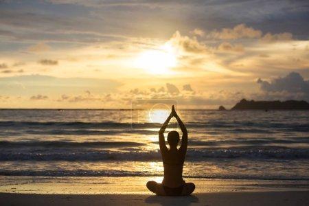 Photo pour Femme blanche pratiquant le yoga au bord de la mer de l'océan tropique - image libre de droit