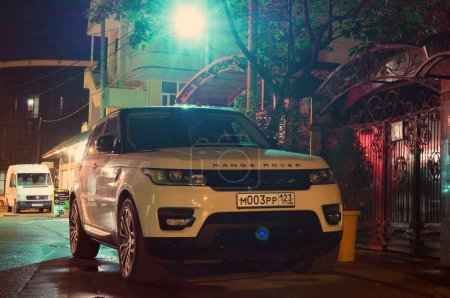 Range Rover parked near house at night.