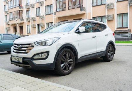 New white Hyundai Santa Fe parked on the street near the house.