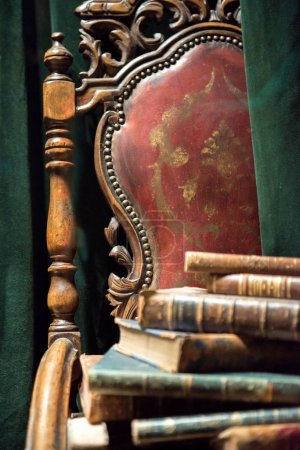 Vintage baroque armchair with old books against green curtain