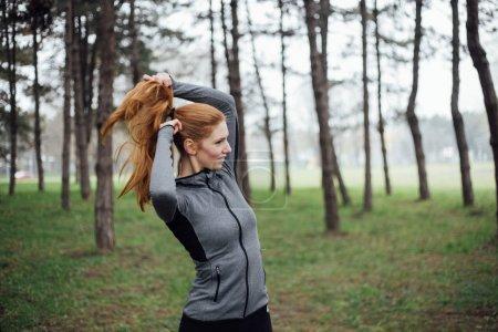 Woman binding hair in park