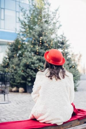 Photo for Young woman in red hat sitting on Christmas fair, back view - Royalty Free Image