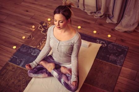woman sitting in lotus asana