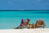 Picture of wooden beach chairs on the tropical beach, vacation.