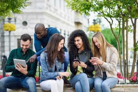 Photo for Multi-ethnic group of young people using smartphone and tablet computers outdoors in urban background. Women and men smiling and laughing in the street wearing casual clothes. - Royalty Free Image