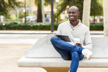 Photo for Black young man with tablet computer and take away coffee in urban background. Young african guy with shaved head wearing casual clothes. - Royalty Free Image