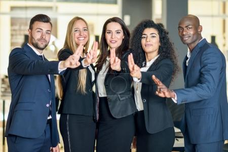 Photo for Group of businesspeople with thumbs up gesture in modern office. Multi-ethnic people working together. Teamwork concept. - Royalty Free Image