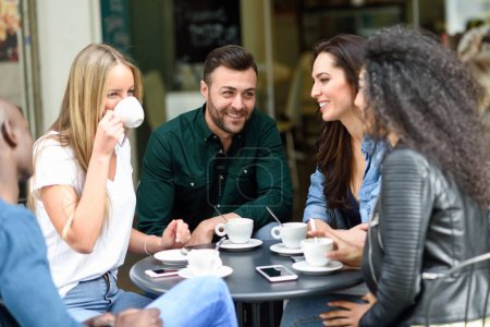 Foto de Grupo multirracial de cinco amigos tomando un café juntos. Tres mujeres y dos hombres en el café, hablando, riendo y disfrutando de su tiempo. Conceptos de estilo de vida y amistad con modelos de personas reales - Imagen libre de derechos