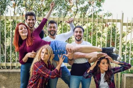 Photo for Group portrait of boys and girls with colorful fashionable clothes holding friend. Urban style people having fun - Concepts about youth and togetherness. - Royalty Free Image