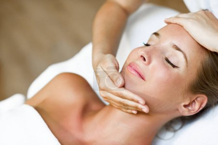 Young woman receiving a head massage in a spa center.