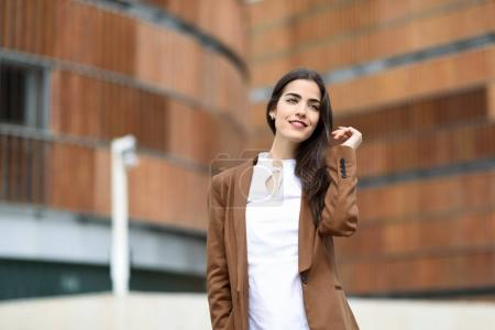 Young woman with nice hair standing outside of office building.