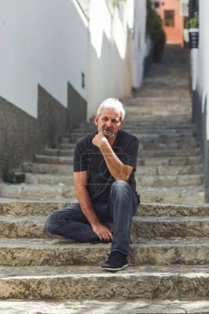 Photo for Mature man sitting on steps in the street. Senior male with white hair and beard wearing casual clothes in urban background. - Royalty Free Image
