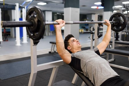 Young man bodybuilder doing weight lifting in gym.