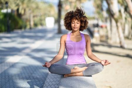 Photo pour Femme noire, coiffure afro, faire du yoga sur la plage avec les yeux fermés. Jeune femme portant des vêtements de sport à la figure de lotus avec fond défocalisé. - image libre de droit