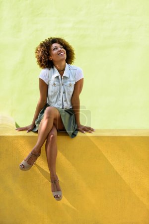 Young black woman, afro hairstyle, sitting on an urban wall