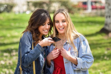 Two young women recording a voice message with smart phone