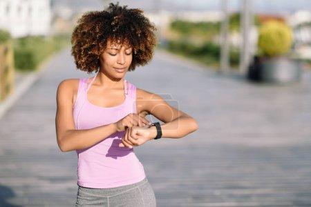 Young black woman using smartwatch touching touchscreen