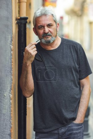 Mature man with grey hair standing in urban background