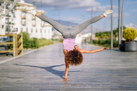 Photo for Black fit woman doing fitness acrobatics in urban background. Young female exercising and working out hard. - Royalty Free Image