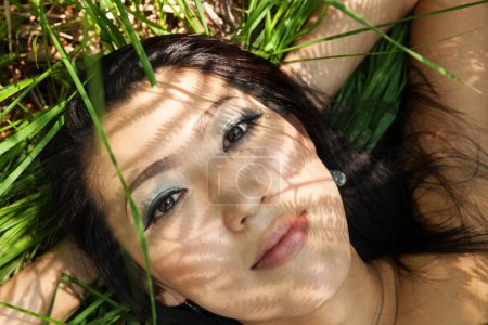 Asian girl portrait outdoors in the ferns shadows