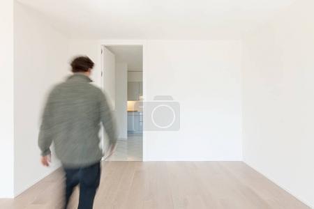 Photo pour Homme de dos marche dans une salle vide - image libre de droit