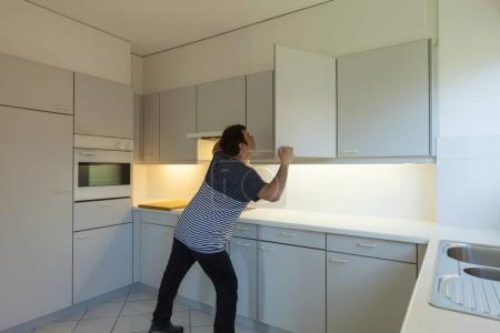 Photo pour Homme bizarre vous cherchez quelque chose dans une cuisine vide - image libre de droit