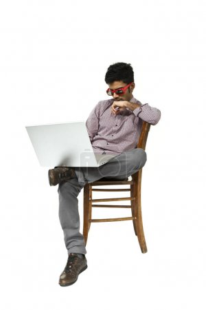 young man portrait working with the laptop sitting on a chair