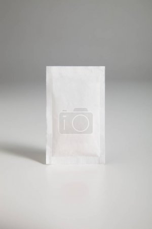 sugar sachet over gray background, close up
